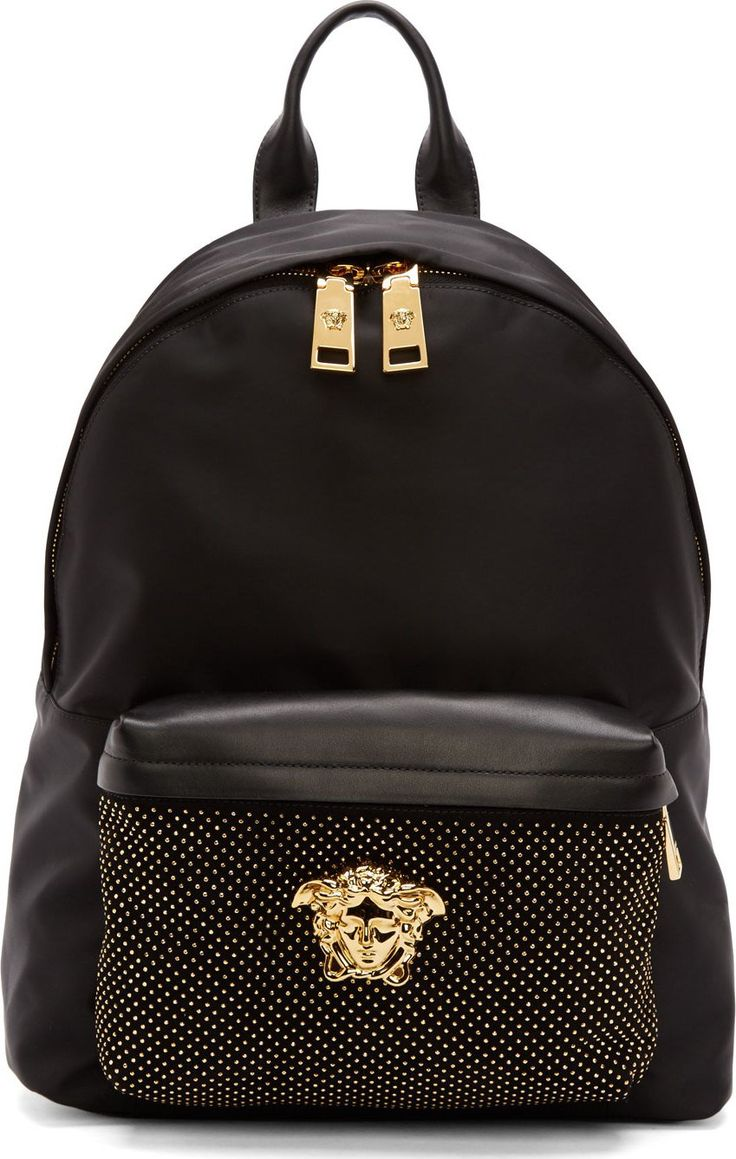 """Versace Medusa Textile backpack in black. Gold-tone hardware. Leather carry handle at top of bag. Adjustable shoulder straps. Zippered compartment at front face in tonal leather and suede featuring micro studs and signature Medusa accent. Two-way zip closure at main compartment. Approx. 12"""" length x 16"""" height x 5"""" width."""
