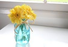 Blue mason jar with yellow gerber daisy and twine.