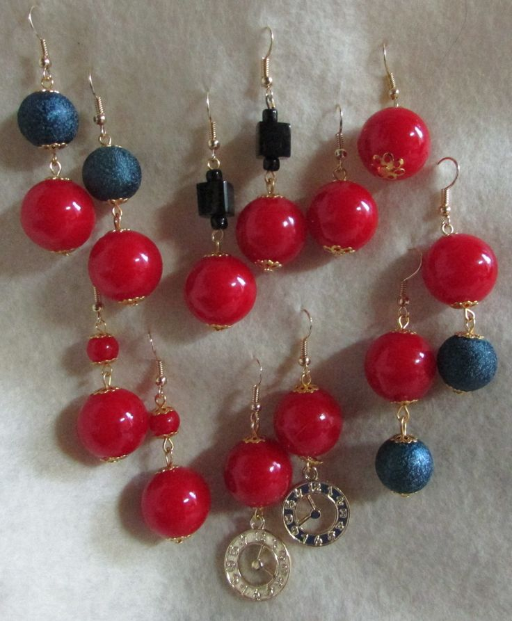 Aros en rojos, bolitas rojo ,azules , cubos cristal negros, charms dorados reloj