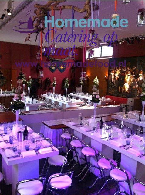 Moderne diner opstelling aan hoge tafel met chroom krukken in de Grote Salon van het Koetshuis van Kasteel Keukenhof. LED verlichting in de kleuren magenta, paars en wit. Gebruik van modern wit meubilair met chroom krukken met witte zitting en hoge witte vazen op tafel. De chef live vanuit open keuken in het midden van de zaal. Homemade Catering op Maat denkt graag mee over de creatieve invulling van uw avond.