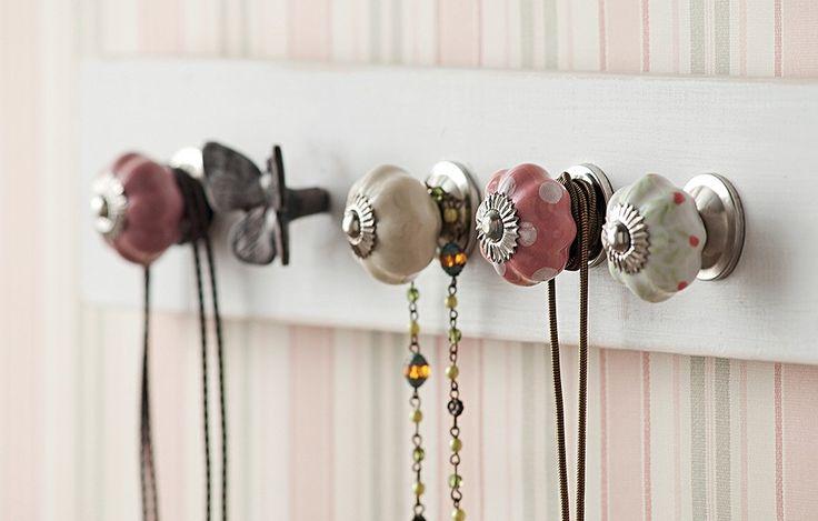 Presos a uma régua de madeira, os puxadores de porcelana e o de ferro em forma de borboleta deixam os colares organizados e à mão: