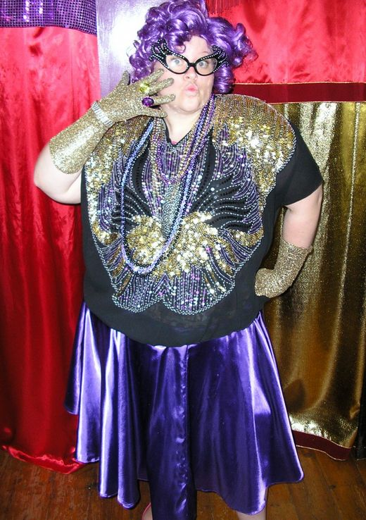 Dame Edna costume available for hire in store. Available in Small, Medium, Large and Extra Large. Costume includes skirt, gloves, jewellery, glasses and wig.