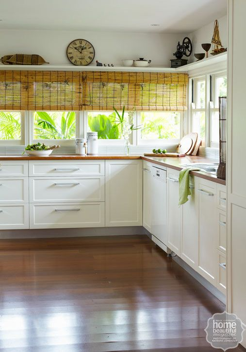 An expanse of windows floods the room with natural light, while a rattan ceiling fan lends a Hawaiian plantation vibe.