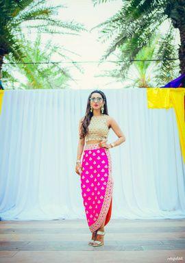 Mehendi Outfits - Harit & Eshanka | WedMeGood | Gold Blouse with Pink One Side Slit Skirt  #wedmegood #indianbride via @topupyourtrip