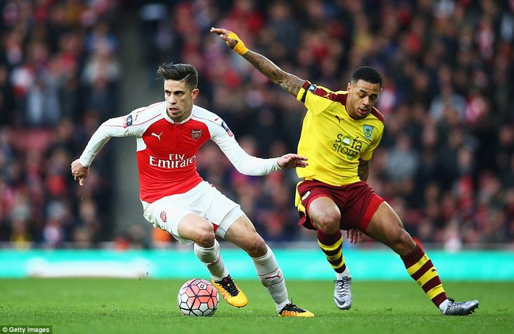 The Gunners' 25-year-old Brazilian Gabriel Paulista (left) takes the ball away from Burnle...