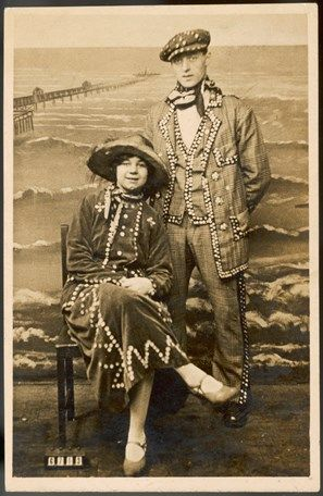 a pearl king and queen with a seaside studio backdrop behind them
