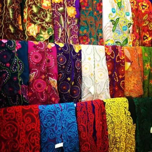 Embroidered cotton fabrics ready to be made into beautiful kebaya - Indonesian traditional blouses. These ones are in a shop on Jalan Sulawesi, Denpasar, Bali, a street renowned for its offerings of traditional attire and a variety of textiles. (Photo by Electra Gillies) #kebaya #Denpasar #Bail #Indonesia