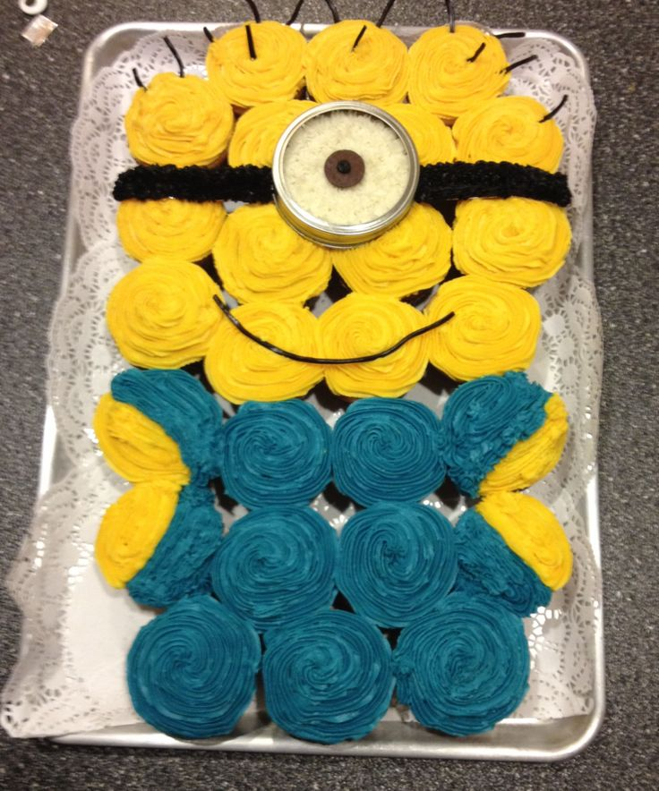 Despicable Me minion cupcake cake. Eye is a mason jar lid with a candy melt for the eye, band for goggles is tin foil covered in frosting & hair is licorice.