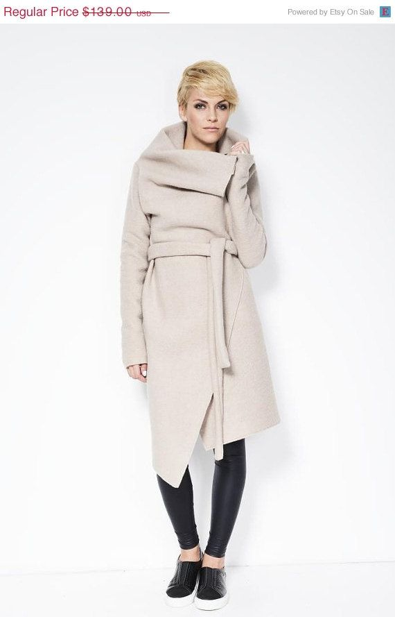 A high collar light coat with a belt, and raw edges. Throw over your favorite top or jacket for an edgy, unique look. Wear the collar high or