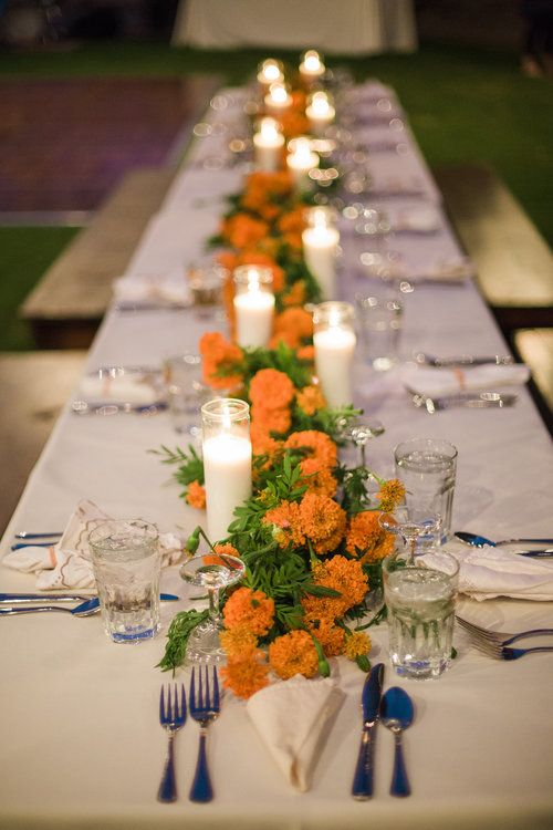 Desert wedding in Joshua Tree at 29 Palms Inn. Marigold garland for the long tables with vintage linen napkins