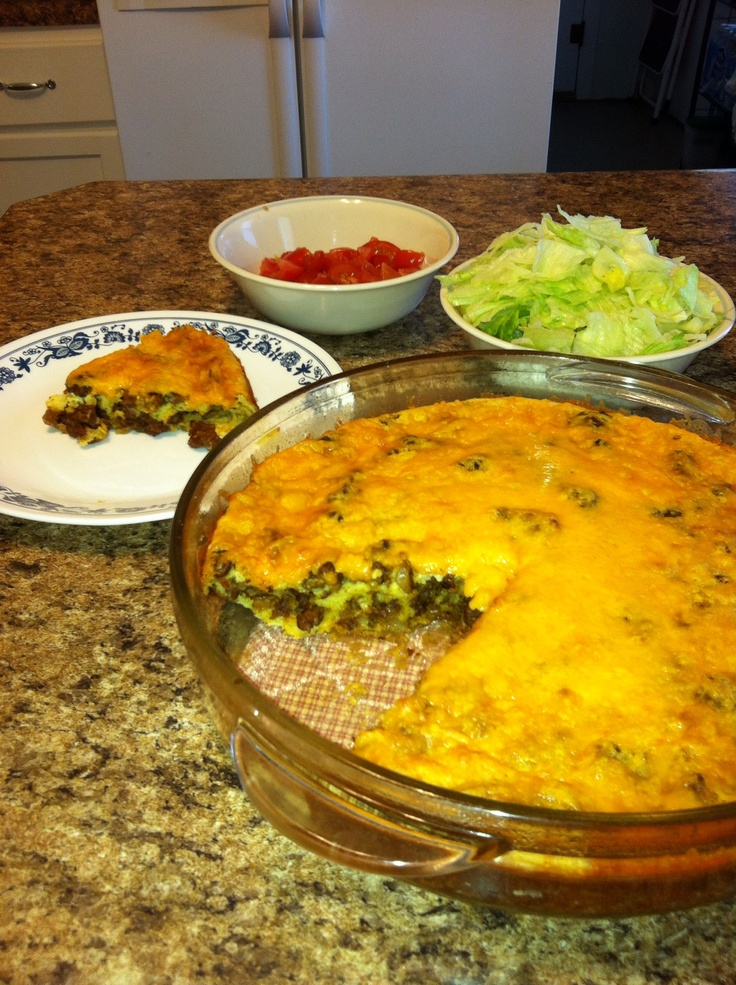 "Easy Taco Pie - 1 lb hamburger, small onion chopped, 1 pkg taco seasoning, 1 1/4 c. milk, 3/4 c. Bisquick, 3 eggs, tomatoes, cheddar cheese, sour cream. Heat oven to 400, grease 10"" dish. Cook beef & onion until cooked thru; drain. Stir in seasoning mix (no water just seasoning powder). Spread meat in baking dish,  mix milk, eggs & bisquick until smooth. Pour over beef. Bake 25 min, top with shredded cheese, bake 8-10 min longer.  Cool 5 min, top with tomatoes/lettuce/sour cream to your…"