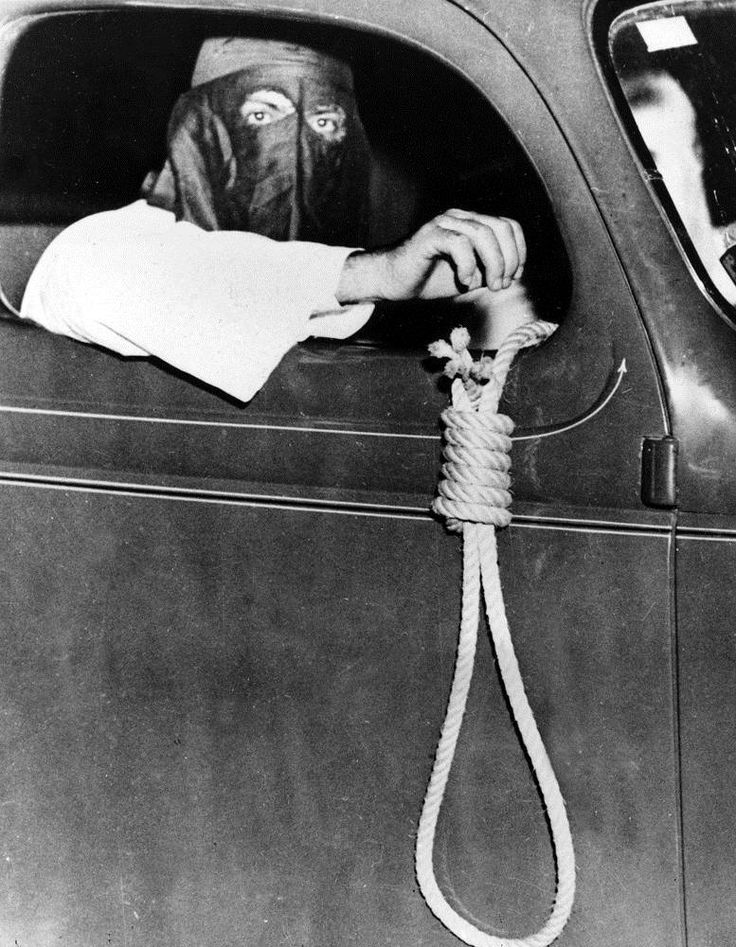 A Ku Klux Klan member dangles a hangman's noose from a car as a warning to blacks to stay away from polling places in the municipal primary in Miami on May 3, 1939. Despite the threats, 616 courageous blacks voted.