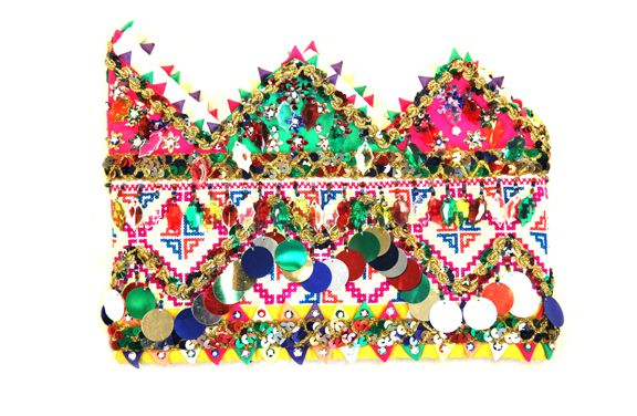 """This hat is a variation of the rooster's comb hat. It was also made in the 1980s by the Hmong people in the refugee camps. Some people refer to this style of hat as a """"crown."""" Such hats were worn for their ornamental effect. It is decorated with appliqué, cross-stitch embroidery, and sequins or small metallic discs. Both the Green and White Hmong women made this style of headdress. It was very popular from the late 1980s into the 1990s."""