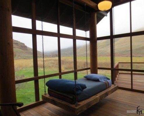 Подвесная кровать с синим покрывалом на веранде