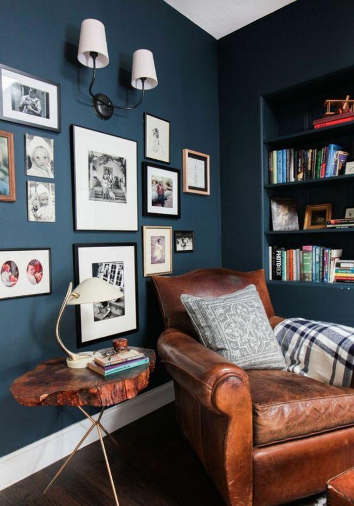 deco salon bleu canard angle de repos et de lecture avec une niche avec des étagères avec des beaucoup de livres et beaucoup de tableaux sur l'autre grand mur en couleur bleu gris