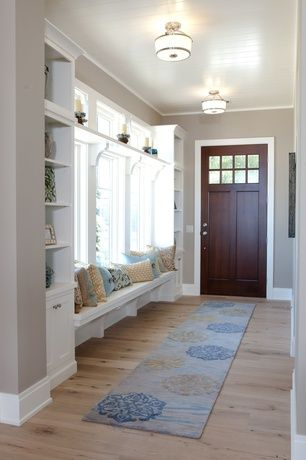 Traditional Entryway with Hardwood floors, Window seat, Glass panel door, Crown molding, Built-in bookshelf, flush light