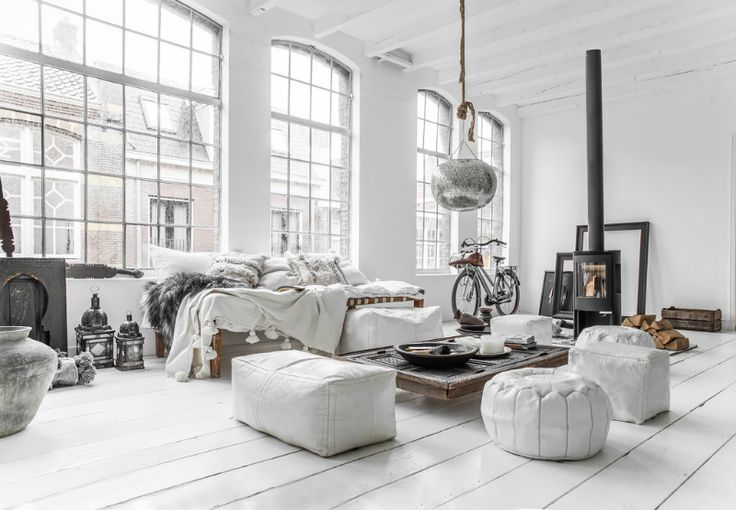 Incredible white loft apartment. I love how the low wood table and floor cushions help the blend the space.