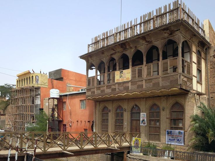 A row of traditional 19th century houses called Shanashels stands along a canal in Basra, Iraq. Abdul Latif Mandel House on the right has an intricate overhanging balcony and pointed windows.