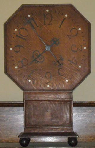 Electric clock, designed 1912,Made from oak which stands on four bronze ball feet. The octagonal face with ivory dots, and the numerals with black wax. (artsandcraftsdesign.com,2017)