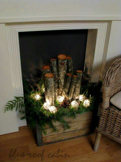 An old crate filled with logs, greens, pine cones, and lights... wouldn't this look great in the house or on the porch by the front door? <3. Courtesy of Mrs. Claus.