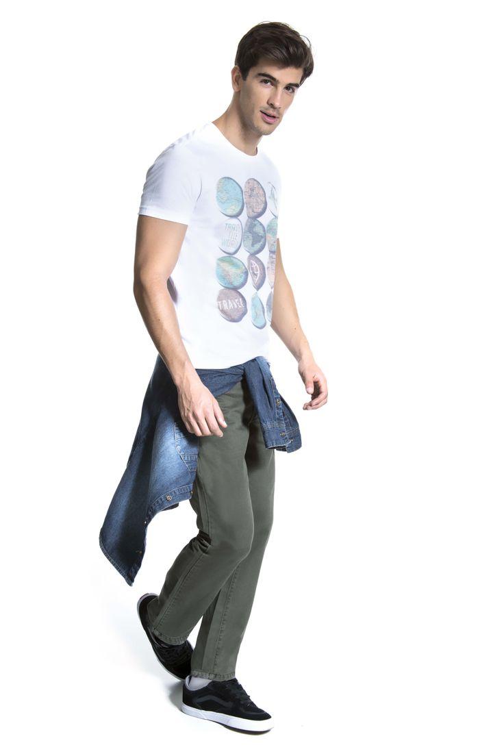 T-shirt estampada com selos de viagem, camisa jeans amarrada no quadril e calça color verde militar.