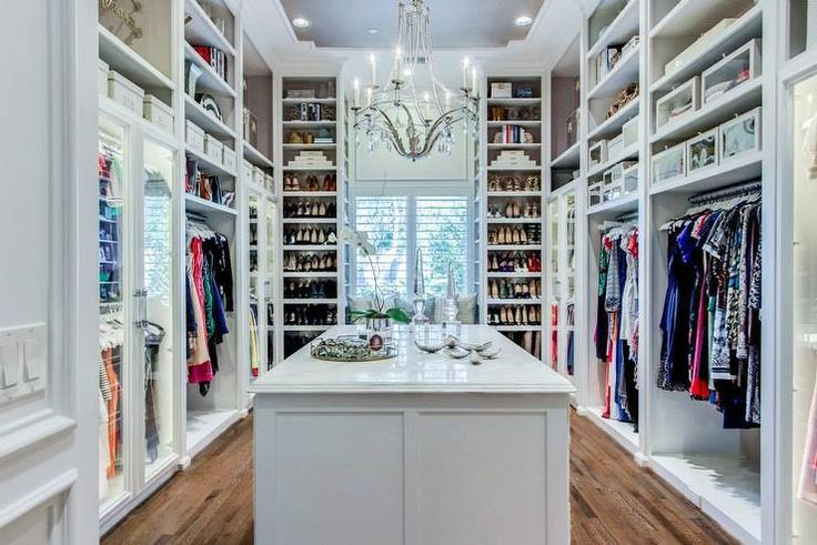 Amazing walk-in closet boasts a crystal droplets chandelier illuminating a marble top closet island fitted with jewelry drawers.