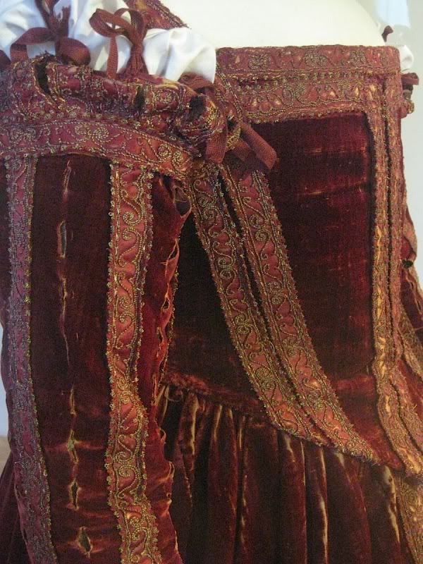 This is the semi extant gown from Pisa. If you click on this you will see that the trim? Is not perfectly placed, in fat it is sometimes allowing the fashion fabric from the gown to show.  Also it has vertical pinks so you would see the under gown's sleeves.     It is on The Ornamented Being's Site: http://ornamentedbeing.tumblr.com/image/7682957052