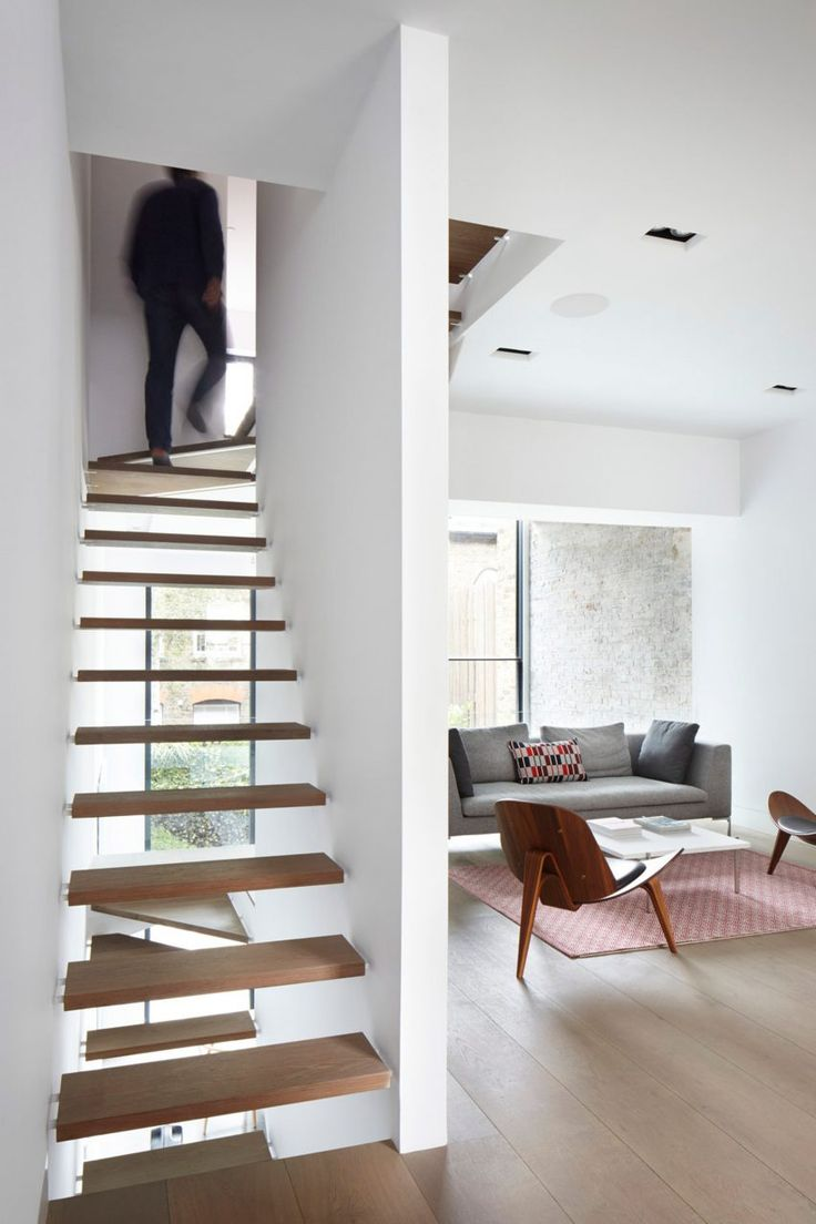 A staircase ascends along one side of this house featuring open wooden treads to maintain