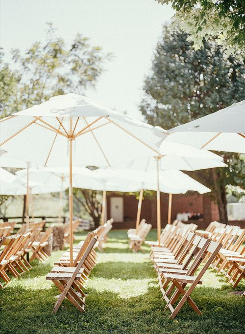 Outdoor summer wedding ceremony at Warrenwood Manor with rustic oak chairs and classic umbrellas. - Photo by Hayes Photo House