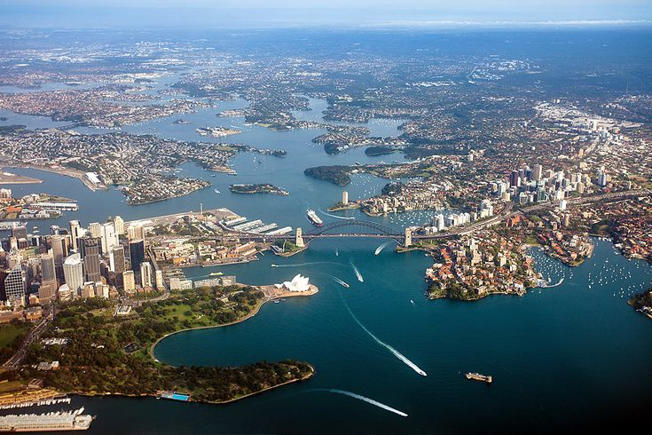 Sydney's CBD on left (southern) side of the Harbour and North Sydney across the Bridge / Sydney Opera House on Bennelong Point and the Royal Botanic Gardens in the foreground.