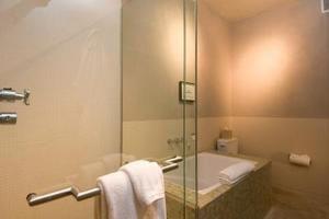 Cómo adherir un panel de ducha de vidrio sin marco a los azulejos