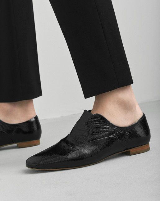 Soft flat shoe with inside elastic. One version in structured patent leather and  one version in goat suede. Thin leather sole and 1,5 cm stacked leather heel.  Lining and insock in goat leather.