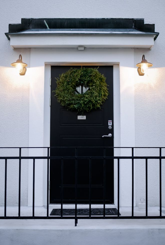 Entrance black door with wreath winter christmastime
