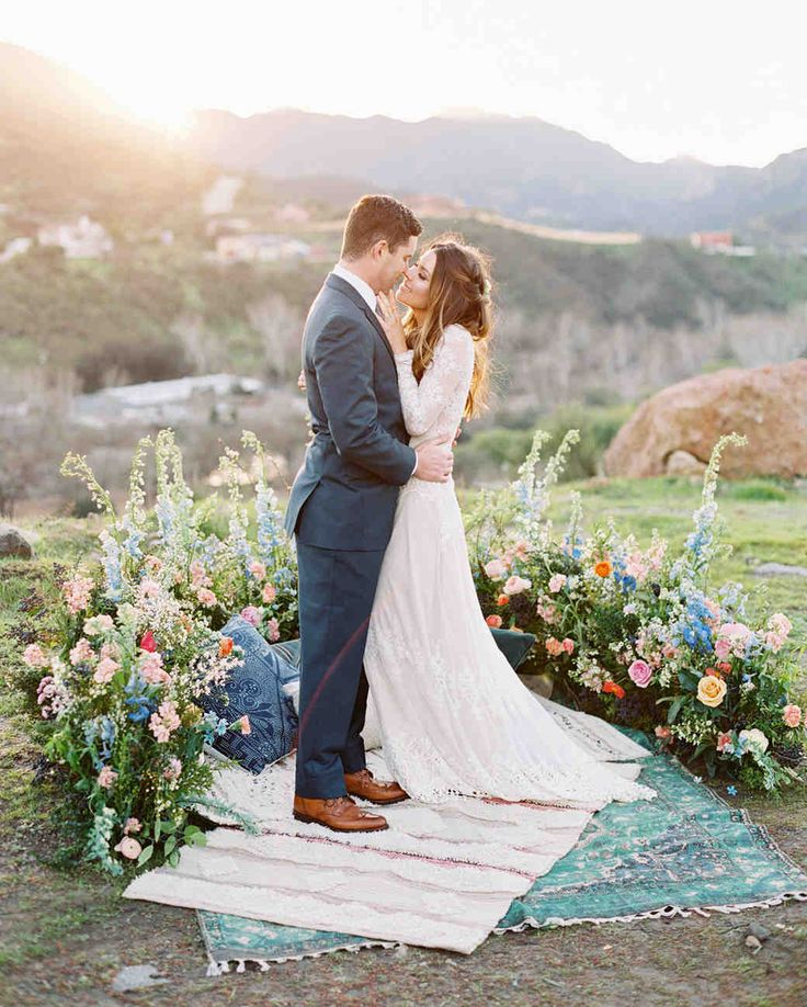 Spring Wedding Ideas from Real Celebrations   Martha Stewart Weddings - Layered rugs, pillows, and a half-circle of assorted wildflowers, roses, and astilbe created this picturesque wedding ceremony spot. #ceremonydecorations #weddingideas #springwedding