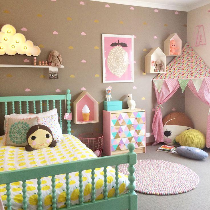 Stanza bambina, stile scandinavo moderno, molto colorata e allegra - colori rosa, verde, giallo e marrone - parete con sticker a forma di piccole nuvole
