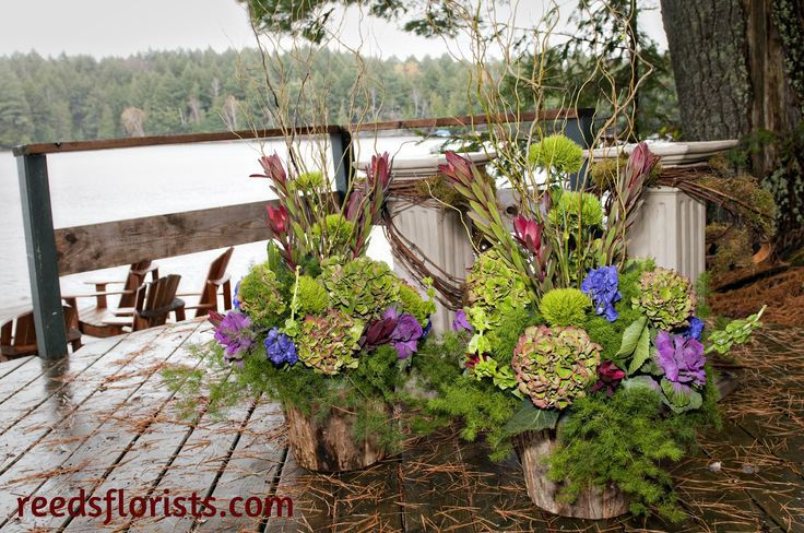 Hazards of a fall wedding in Algonquin Park. Beautiful arrangements for the wedding on the dock take shelter under a tree while a storm blows through.