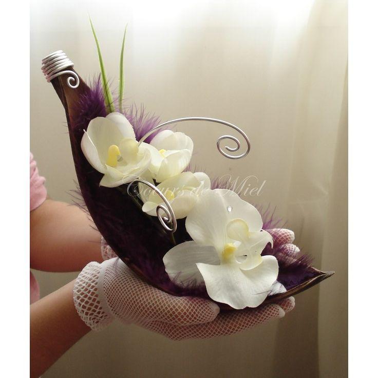 Raffiné et délicat, ce porte alliance sera idéal pour un mariage au thème elfique et oriental. Réalisé à partir d'une coque de Maripa (coque coco), ce coussin d'alliance est orné de plumes et d'une branche d'orchidée. Vous pourrez y maintenir vos alliances grâce aux arabesques.