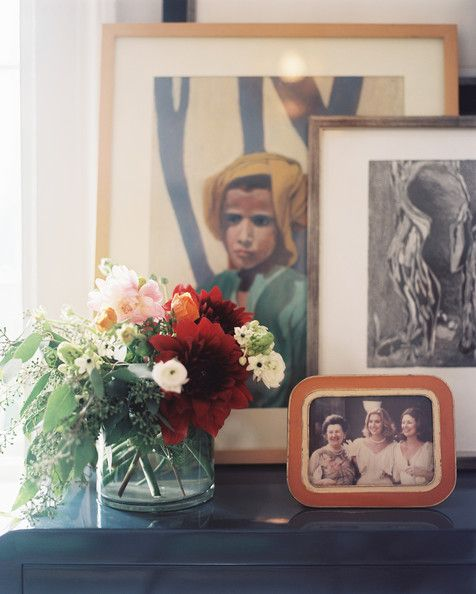 Tablescape Photo - Artwork and a vase of flowers on a blue console