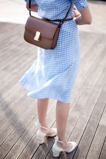 Look we love: gingham dress with a brown crossover purse and simple white heels.