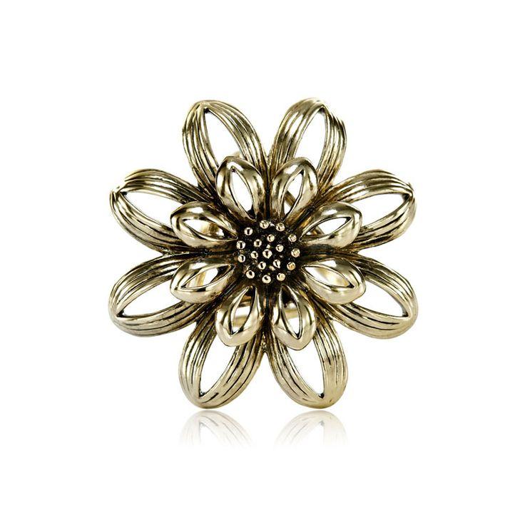 Tento jedinečný zlatý kvetinový prstenec k hodvábnym šatkám a šálom ponúka prírodnou inšpirovaný dizajn s malým okrúhlym kvetom. Kvetinový prstenec obsahuje trojitý krúžok na zadnej strane, aby bolo možné uviazať ho na hodvábnu šatku alebo šál. Kvetinový prstenec je vyrobený z kvalitných materiálov (zliatín), ktoré sú následne pozlátené. Ozdoba sa radí medzi poloklenoty.