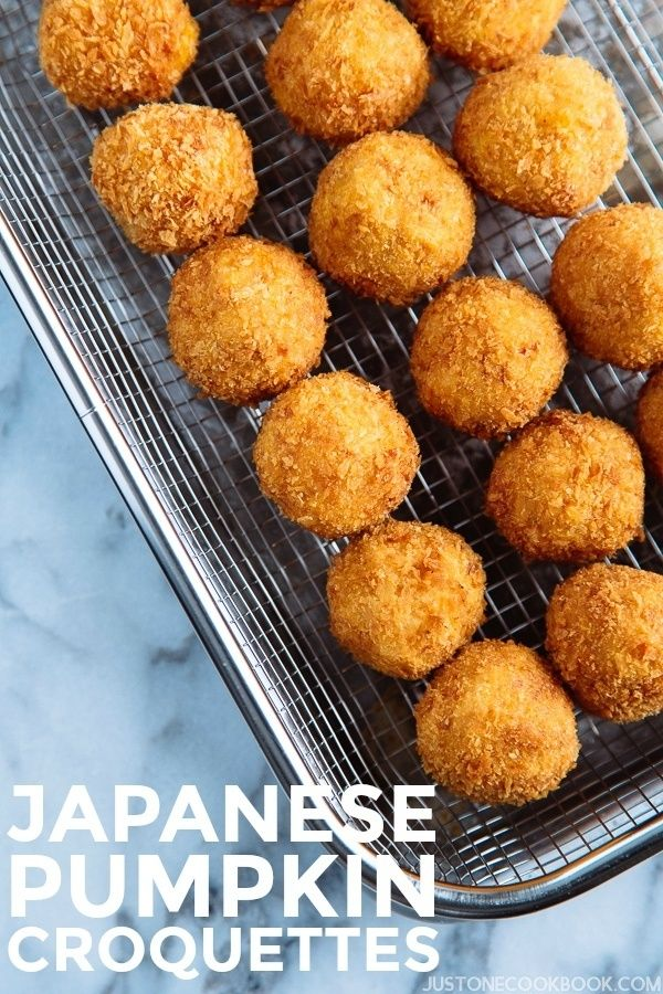 A wire rack containing small ball shape Japanese pumpkin croquettes (kabocha korokke).