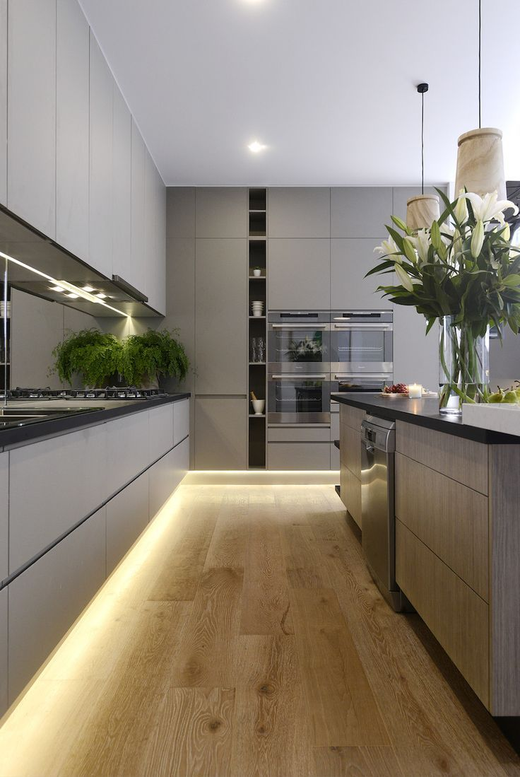 Contemporary grey kitchen with downlit wooden floor boards.