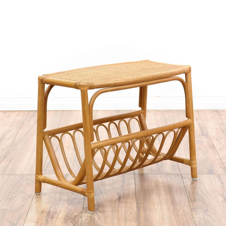 This tropical magazine rack is featured in a rattan with a glossy light wood finish. This side table has a woven wicker table top, a bottom magazine rack and curved accents. Bohemian end table perfect for storing knitting supplies! #bohemian #tables #endtable #sandiegovintage #vintagefurniture