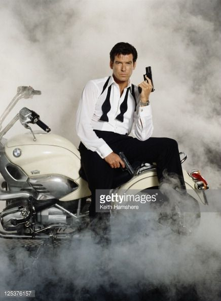 Irish actor Pierce Brosnan stars as 007 in the James Bond film 'Tomorrow Never Dies' 1997 He is sitting on a BMW R1200C and holding a Walther P99...