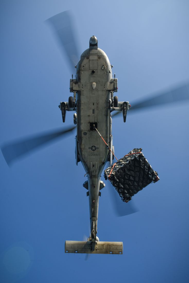 """An MH-60S Seahawk from the """"Indians"""" of HSC-6 carries cargo to USS Theodore Roosevelt (CVN 71) during a replenishment-at-sea. (U.S. Navy photo by Mass Communication Specialist 3rd Class Alex Perlman/Released) ARABIAN GULF – (Dec. 21, 2017) –"""