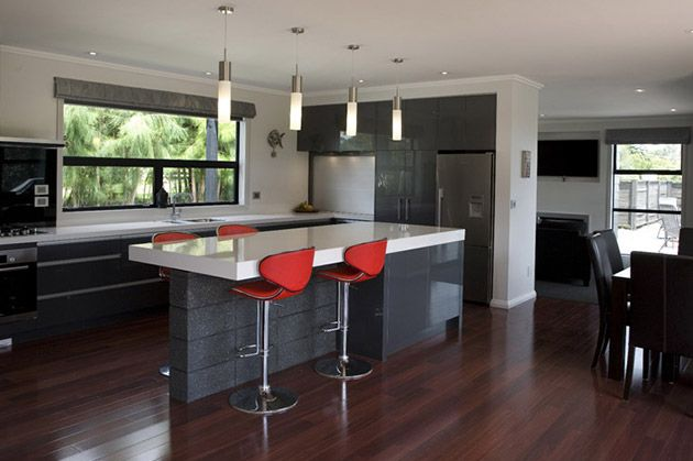 Modern, clean lines are used in this entertainer's kitchen. Dark wooden floors complement the funky, charcoal grey concrete-style kitchen island, finished off by a splash of Hot Red coloured bar stools. #ClassicBuilders #KitchenDesign