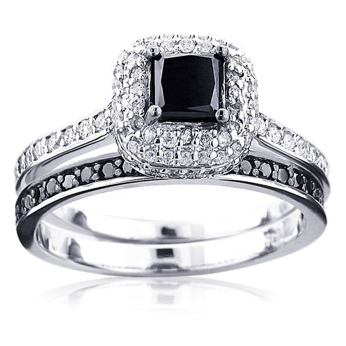 This 10K Gold Black Diamond Unique Bridal Engagement Ring Set consists of a diamond engagement ring and matching band. The engagement ring showcases a 0.5 carat princess cut black diamond in the center and 0.48 carats of round diamonds on the sides for a total of 0.98 carat of dazzling diamonds. The band showcases 0.21 carats of dazzling round black diamonds. This set is available in 10k, 14k or 18k yellow, rose, white gold, various sizes, and can be customized with any color diamonds…