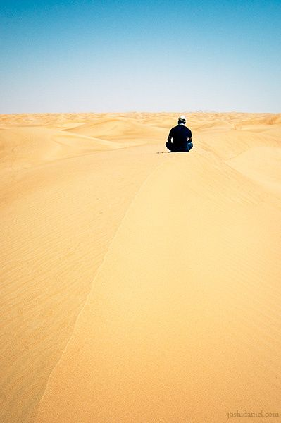 Photograph of Dinu Varghese sitting on a sand dune in United Arab Emirates