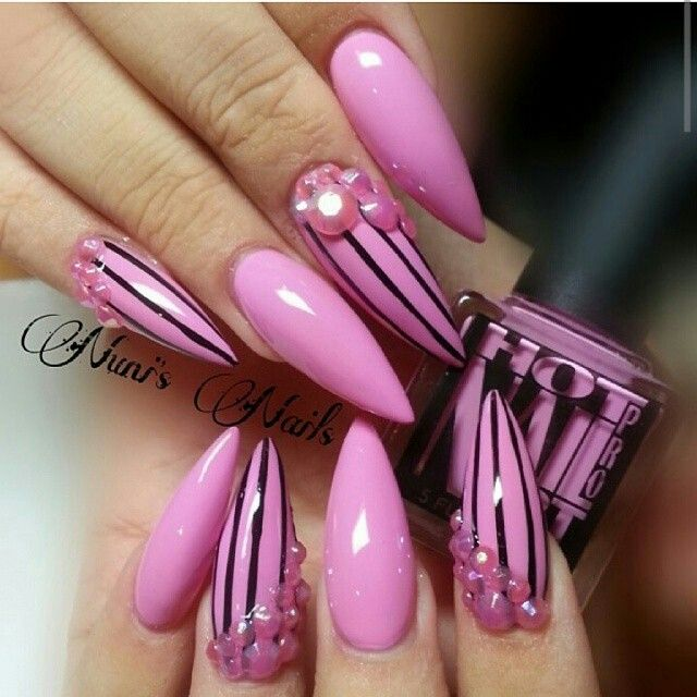Pink stiletto nails with black stripes and pink pearl design- looks like a…