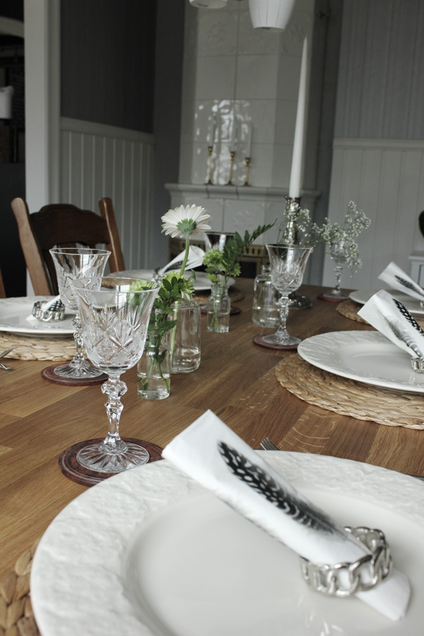 Table setting with flowers and feather on napkin